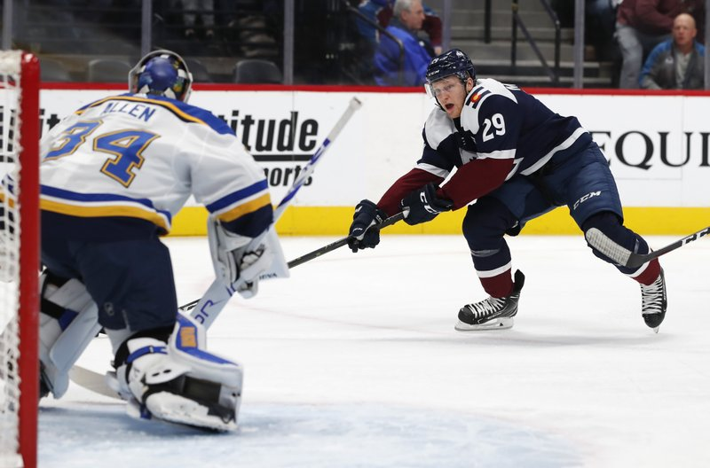 Colorado Avalanche center Nathan MacKinnon, right, looks to shoot the puck at St. Louis Blues goaltender Jake Allen during the first period of an NHL hockey game Friday, Nov. 30, 2018, in Denver. (AP Photo/David Zalubowski)