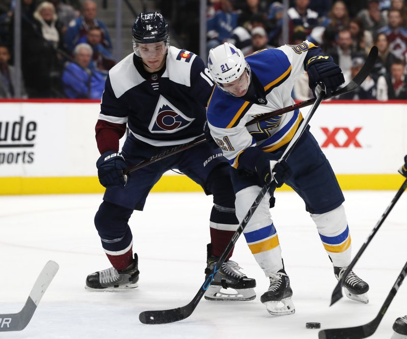 Colorado Avalanche defenseman Nikita Zadorov, left, uses his stick to slow down St. Louis Blues center Tyler Bozak, who tries to puck the put on the net during the second period of an NHL hockey game Friday, Nov. 30, 2018, in Denver. (AP Photo/David Zalubowski)