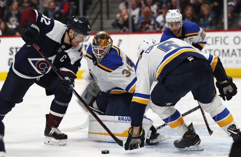 Colorado Avalanche left wing Gabriel Landeskog, left, tries to redirect the puck past St. Louis Blues goaltender Jake Allen, center, and defenseman Joel Edmundson during the third period of an NHL hockey game Friday, Nov. 30, 2018, in Denver. The Blues won 3-2 in overtime. (AP Photo/David Zalubowski)