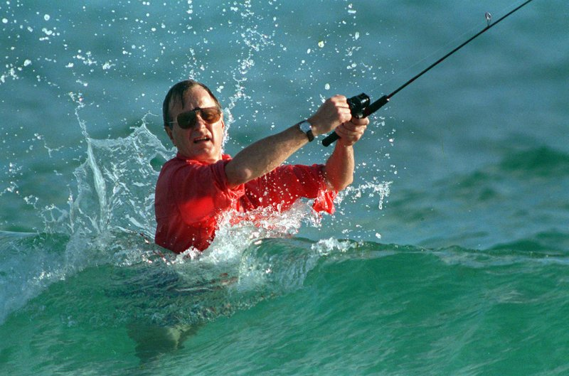FILE - In this Nov. 12, 1988, file photo, waves splash on then-President-elect George H.W. Bush as he casts a line while fishing in Gulf Stream, Fla. Bush died at the age of 94 on Friday, Nov. 30, 2018, about eight months after the death of his wife, Barbara Bush. (AP Photo/Kathy Willens, File)
