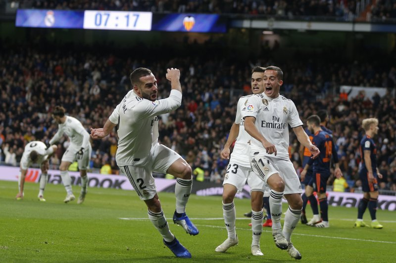 Real Madrid's Dani Carvajal, left, celebrates after Valencia's Daniel Wass scored an own goal during a Spanish La Liga soccer match between Real Madrid and Valencia at the Santiago Bernabeu stadium in Madrid, Spain, Saturday, Dec. 1, 2018. (AP Photo/Paul White)