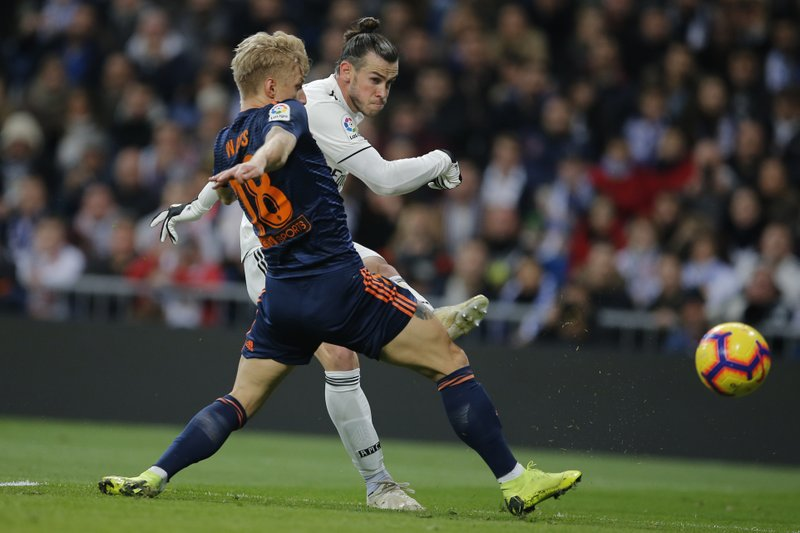 Real Madrid's Gareth Bale, right, shoots past Valencia's Daniel Wass during a Spanish La Liga soccer match between Real Madrid and Valencia at the Santiago Bernabeu stadium in Madrid, Spain, Saturday, Dec. 1, 2018. (AP Photo/Paul White)