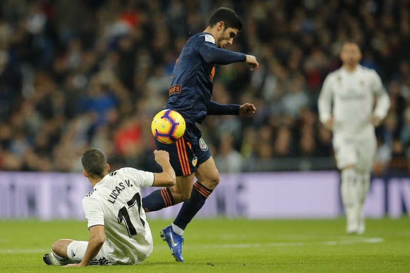 Valencia's Goncalo Guedes, centre, and Real Madrid's Lucas Vazquez vie for the ball during a Spanish La Liga soccer match between Real Madrid and Valencia at the Santiago Bernabeu stadium in Madrid, Spain, Saturday, Dec. (AP Photo/Paul White)