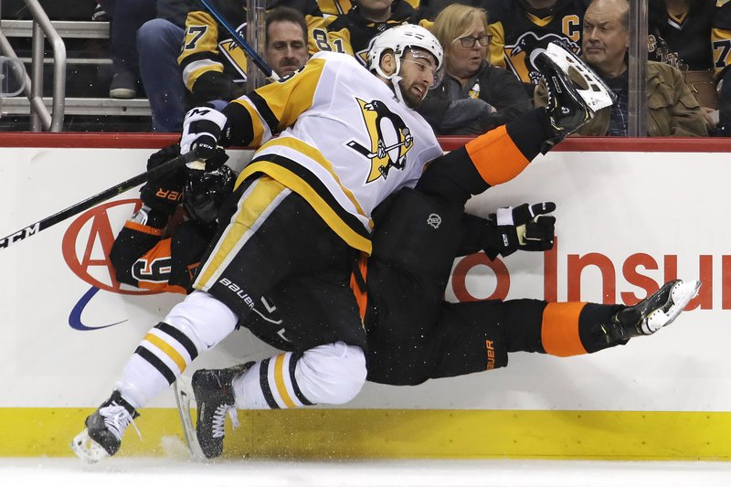 Pittsburgh Penguins' Zach Aston-Reese (46) checks Philadelphia Flyers' Ivan Provorov (9) into the boards during the second period of an NHL hockey game in Pittsburgh, Saturday, Dec. 1, 2018. (AP Photo/Gene J. Puskar)