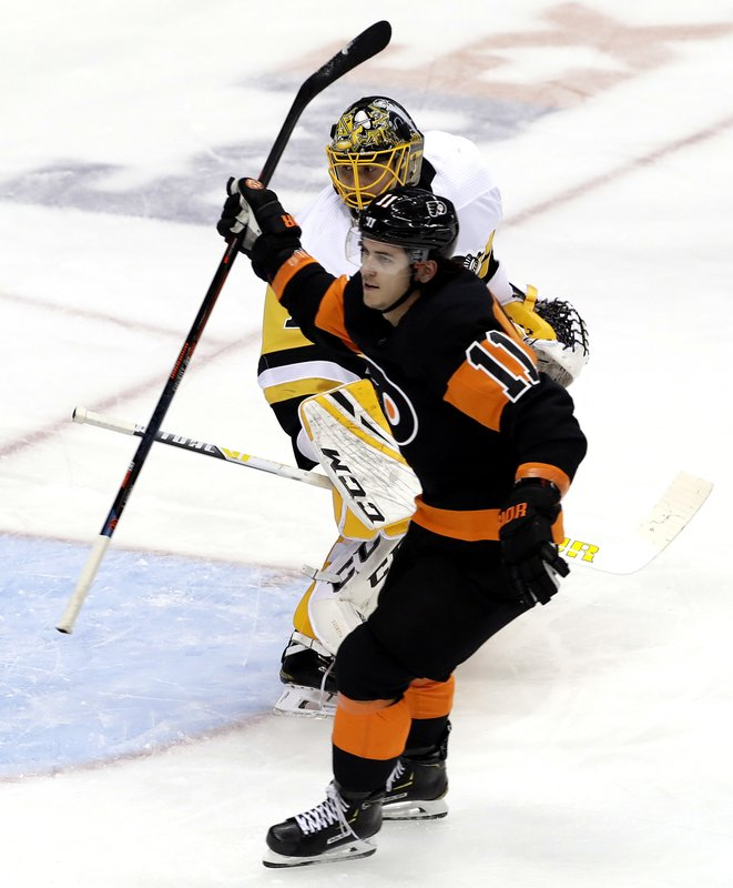 Philadelphia Flyers' Travis Konecny (11) celebrates as he skates past Pittsburgh Penguins goaltender Casey DeSmith (1) after scoring in the first period of an NHL hockey game in Pittsburgh, Saturday, Dec. 1, 2018. (AP Photo/Gene J. Puskar)