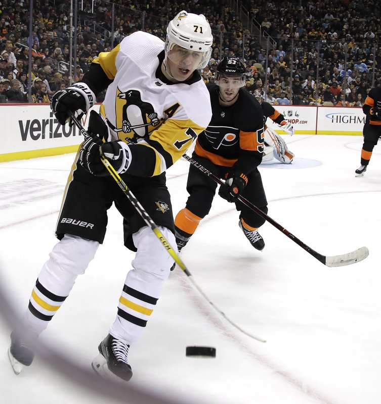 Pittsburgh Penguins' Evgeni Malkin (71) knocks the puck out of the air with Shayne Gostisbehere (53) defending during the second period of an NHL hockey game in Pittsburgh, Saturday, Dec. 1, 2018. (AP Photo/Gene J. Puskar)