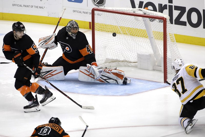 Pittsburgh Penguins' Sidney Crosby (87) puts the puck behind Philadelphia Flyers goaltender Anthony Stolarz (41) with Shayne Gostisbehere (53) defending during the first period of an NHL hockey game in Pittsburgh, Saturday, Dec. 1, 2018. (AP Photo/Gene J. Puskar)
