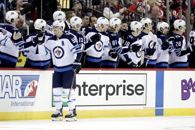 Winnipeg Jets center Mark Scheifele skates by his bench after scoring a goal against the New Jersey Devils during the second period of an NHL hockey game, Saturday, Dec. 1, 2018, in Newark, N.J. (AP Photo/Julio Cortez)