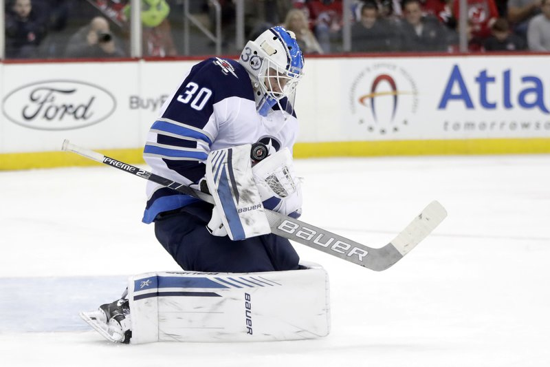 Winnipeg Jets goaltender Laurent Brossoit blocks a shot from the New Jersey Devils during the second period of an NHL hockey game, Saturday, Dec. 1, 2018, in Newark, N.J. (AP Photo/Julio Cortez)