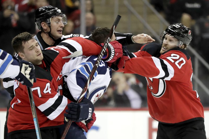 Winnipeg Jets left wing Brandon Tanev, center, gets into a scuffle with New Jersey Devils defenseman Egor Yakovlev (74), of Russia, and center Blake Coleman (20) during the first period of an NHL hockey game, Saturday, Dec. 1, 2018, in Newark, N.J. (AP Photo/Julio Cortez)