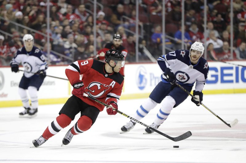 New Jersey Devils left wing Taylor Hall, center, skates with the puck next to Winnipeg Jets center Adam Lowry during the first period of an NHL hockey game Saturday, Dec. 1, 2018, in Newark, N.J. (AP Photo/Julio Cortez)