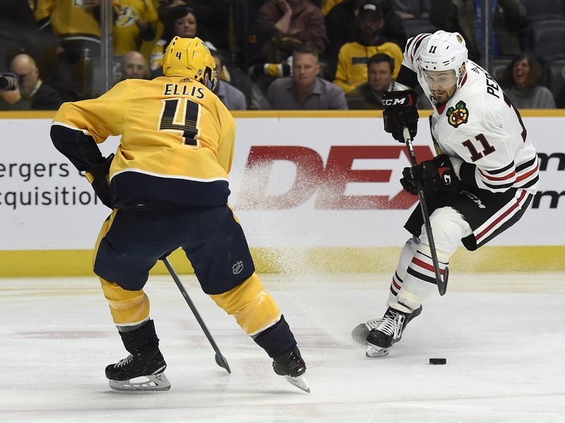 Chicago Blackhawks left wing Brendan Perlini (11), of Britain, moves the puck as he is defended by Nashville Predators defenseman Ryan Ellis (4) during the first period of an NHL hockey game Saturday, Dec. 1, 2018, in Nashville, Tenn. (AP Photo/Mark Zaleski)