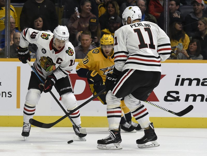 Chicago Blackhawks center Jonathan Toews (19) controls the puck in front of Nashville Predators right wing Miikka Salomaki (20), of Finland, as left wing Brendan Perlini (11), of Britain, moves in during the first period of an NHL hockey game Saturday, Dec. 1, 2018, in Nashville, Tenn. (AP Photo/Mark Zaleski)