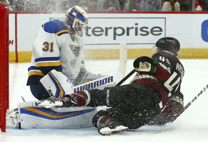Arizona Coyotes right wing Josh Archibald, right, crashes into St. Louis Blues goaltender Chad Johnson (31) as Johnson makes a save on a shot during the second period of an NHL hockey game, Saturday, Dec. 1, 2018, in Glendale, Ariz. (AP Photo/Ross D. Franklin)