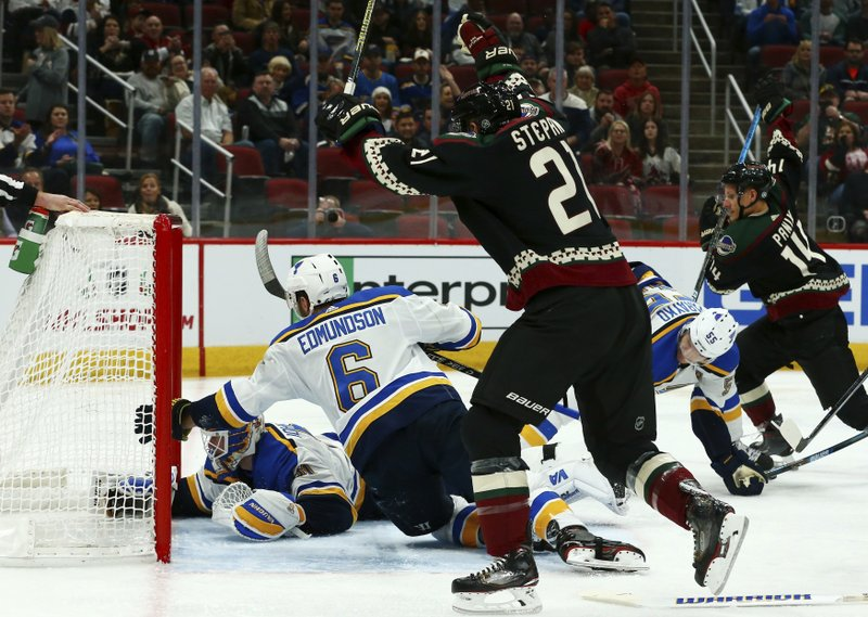 St. Louis Blues goaltender Chad Johnson, left, defenseman Joel Edmundson (6) and Blues defenseman Colton Parayko (55) are unable to stop a goal by Arizona Coyotes' Christian Fischer as Coyotes center Derek Stepan (21) and Coyotes right wing Richard Panik (14) celebrate during the second period of an NHL hockey game, Saturday, Dec. 1, 2018, in Glendale, Ariz. (AP Photo/Ross D. Franklin)