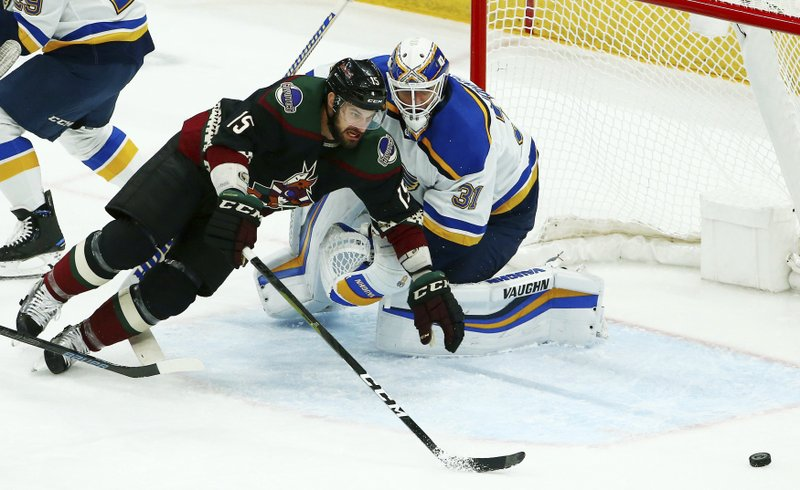 Arizona Coyotes center Brad Richardson (15) gets tripped up as he goes for the puck in front of St. Louis Blues goaltender Chad Johnson (31) during the first period of an NHL hockey game, Saturday, Dec. 1, 2018, in Glendale, Ariz. (AP Photo/Ross D. Franklin)
