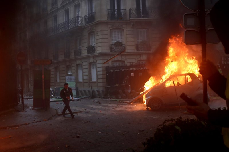 A demonstrator runs pas a burning car during a demonstration Saturday, Dec.1, 2018 in Paris. Protesters angry about rising taxes clashed with French police for a third straight weekend and over 100 were arrested after pockets of demonstrators built barricades in the middle of streets in central Paris, lit fires and threw rocks at officers Saturday. (AP Photo/Thibault Camus)