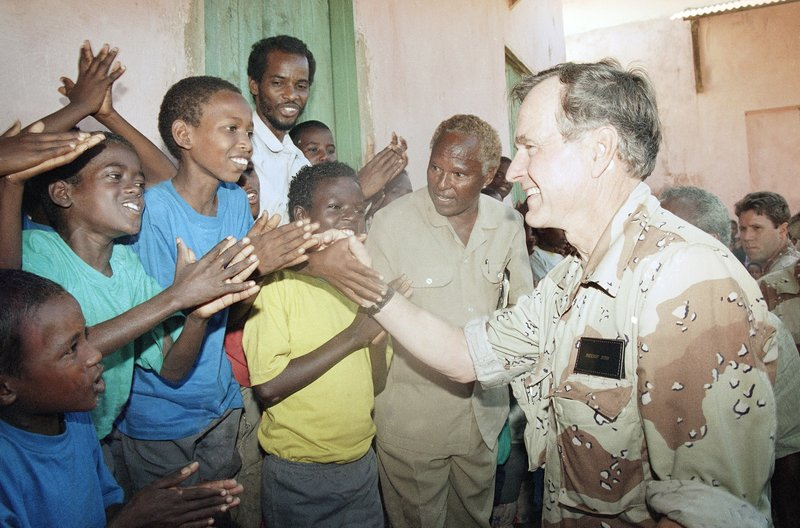 FILE - In this Friday, Jan. 1, 1993 file photo, U.S. President George H.W. Bush greets Somali children applauding him during a visit to an orphanage in famine-ravaged Baidoa, Somalia on a two-day visit to review Operation Restore Hope. In the final days of his presidency, George H.W. Bush committed the U.S. military to a mission many would later regret, ordering more than 20,000 troops into Somalia to