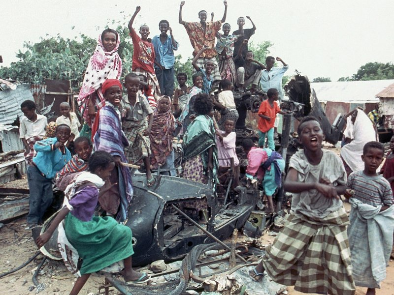 FILE - In this Oct. 19, 1993 file photo, a group of young Somalis chant anti-American slogans while sitting atop the burned out hulk of a U.S. Black Hawk helicopter, shot down during a firefight with Somali guerrillas, in Mogadishu, Somalia. In the final days of his presidency, George H.W. Bush committed the U.S. military to a mission many would later regret, ordering more than 20,000 troops into Somalia to