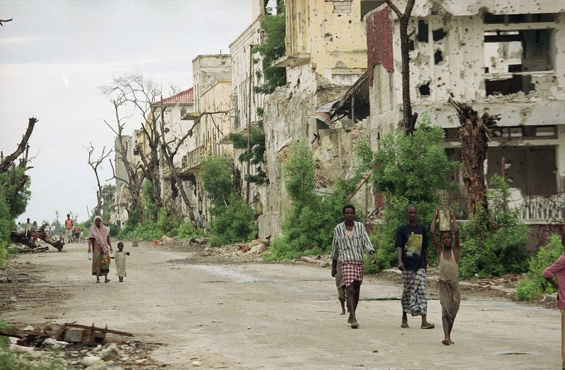 FILE - In this Thursday, Dec. 10, 1992 file photo, Somalis walk on a street in Mogadishu, Somalia that divides the capital between north and south and fighting clans in what is known as the Green Line. In the final days of his presidency, George H.W. Bush committed the U.S. military to a mission many would later regret, ordering more than 20,000 troops into Somalia to