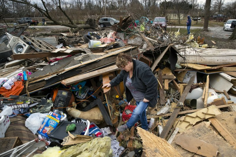 Joyce Morrissey sorts through the debris of her nephew Stephen Tirpak's house in Taylorville, Ill., Sunday, Dec. 2, 2018. The National Weather Service says multiple tornadoes touched down in central Illinois, damaging dozens of structures and injuring multiple people. (Ted Schurter/The State Journal-Register via AP)