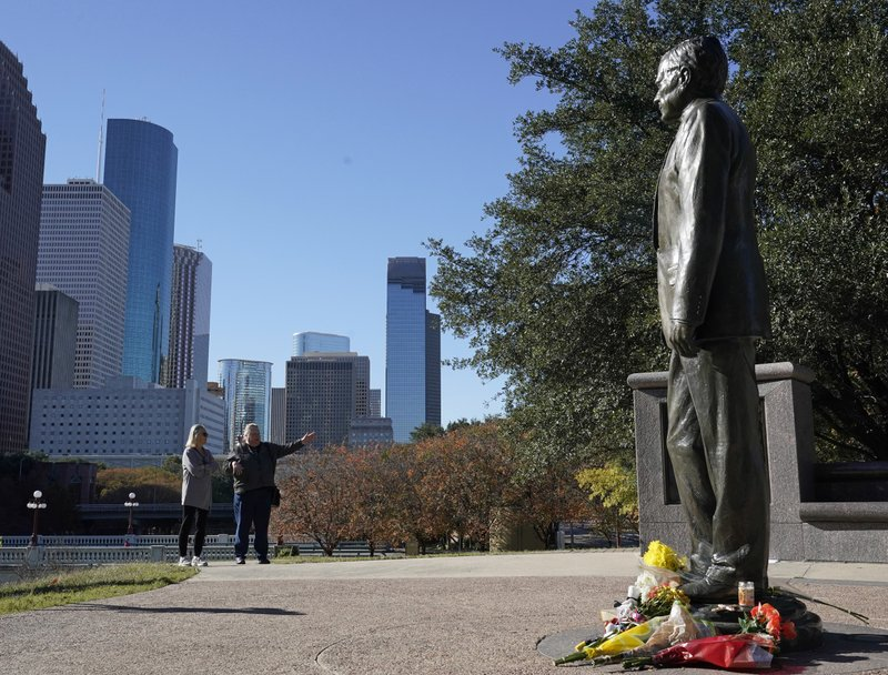 Deitz Kracker, left, and Marg Frazier visit a statue of former President George H.W. Bush in downtown Houston, Sunday, Dec. 2, 2018. Bush is returning to Washington as a revered political statesman, hailed by leaders across the political spectrum and around the world as a man not only of greatness but also of uncommon decency and kindness.  Bush, died late Friday at his Houston home at age 94, is to be honored with a state funeral at National Cathedral in the nation's capital on Wednesday, followed by burial Thursday on the grounds of his presidential library at Texas A&M. (AP Photo/David J. Phillip)