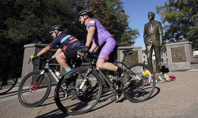 A group of cyclists ride past a statue of former President George H.W. Bush in downtown Houston, Sunday, Dec. 2, 2018. Bush is returning to Washington as a revered political statesman, hailed by leaders across the political spectrum and around the world as a man not only of greatness but also of uncommon decency and kindness.  Bush, died late Friday at his Houston home at age 94, is to be honored with a state funeral at National Cathedral in the nation's capital on Wednesday, followed by burial Thursday on the grounds of his presidential library at Texas A&M. (AP Photo/David J. Phillip)
