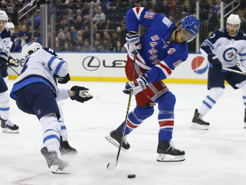 New York Rangers defenseman Marc Staal (18) controls the puck against Winnipeg Jets defenseman Josh Morrissey during the second period of an NHL hockey game, Sunday, Dec. 2, 2018, in New York. (AP Photo/Noah K. Murray)