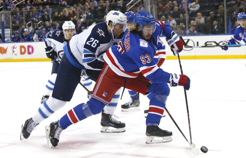 New York Rangers center Mika Zibanejad (93) and Winnipeg Jets right wing Blake Wheeler (26) battle for the puck during the first period of an NHL hockey game, Sunday, Dec. 2, 2018, in New York. (AP Photo/Noah K. Murray)