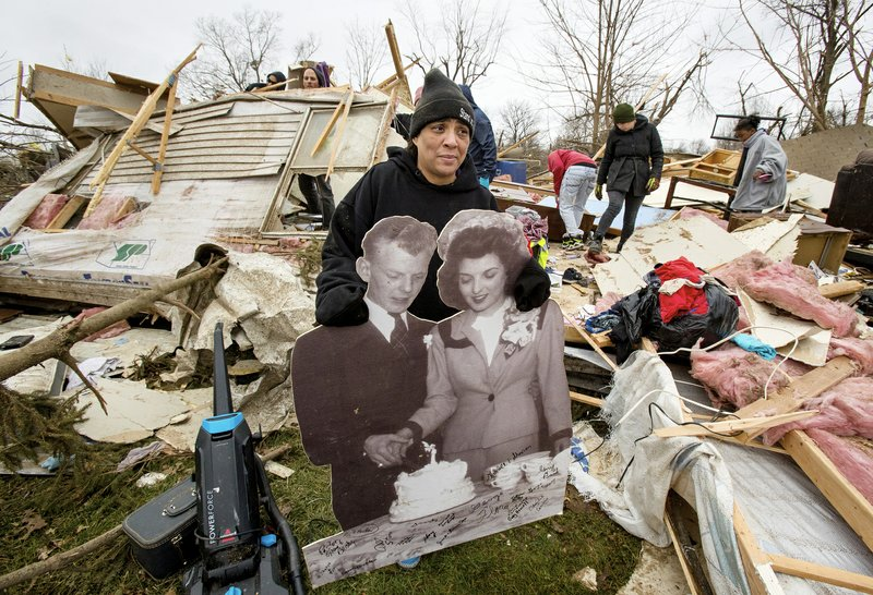 Tiffani Bailey carries an enlarged wedding photo of her grandparents, Charles and Betty Bailey, from the debris of her destroyed home in Taylorville. Bailey, who was in the trailer with her son and mom when it was hit, damaged her ribs and needed more than 30 stitches.