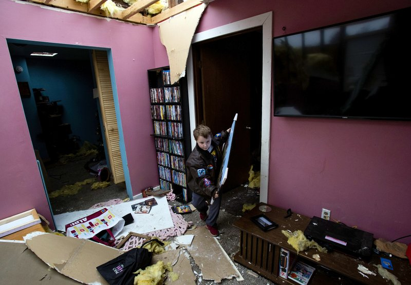David Bowers retrieves items from the interior of his tornado damaged Taylorville, Ill., home Sunday, Dec. 2, 2018. The roof of the home was completely torn off by the storm. (Ted Schurter/The State Journal-Register via AP)