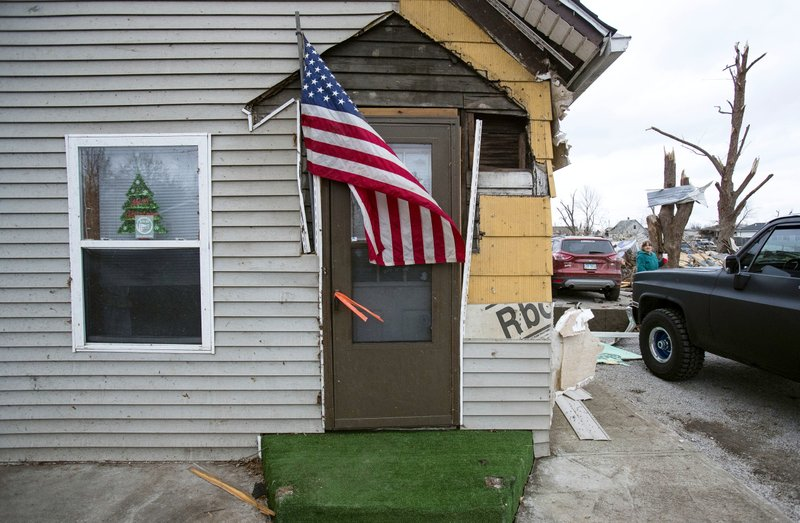Pete Barker of Harrisburg, Ill., wedged a makeshift flag pole in the front of his parent's tornado-damaged house in Taylorville, Ill., Sunday, Dec. 2, 2018. Barker said his dad, a Vietnam veteran who is hospitalized for a heart attack he suffered during the storm, always had flags here.  (Ted Schurter/The State Journal-Register via AP)