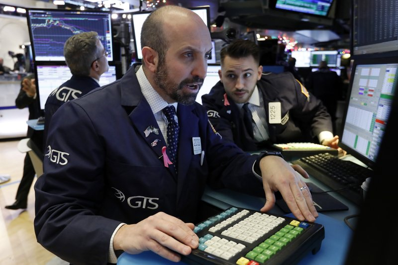 Specialists James Denaro, center, and Matthew Greiner work on the floor of the New York Stock Exchange, Monday, Dec. 3, 2018. Stocks are opening sharply higher on Wall Street, following gains in overseas markets after the U.S. and China struck a 90-day truce in their trade dispute. (AP Photo/Richard Drew)