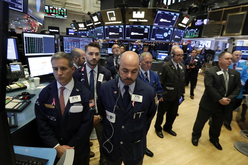 Traders on the floor of the New York Stock Exchange pause for a moment of silence to honor former President George H.W. Bush, Monday, Dec. 3, 2018. (AP Photo/Richard Drew)