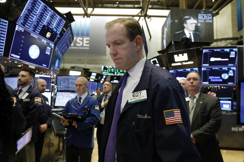 Traders on the floor of the New York Stock Exchange, including Michael Smyth, center, pause for a moment of silence to honor former President George H.W. Bush, Monday, Dec. 3, 2018. (AP Photo/Richard Drew)