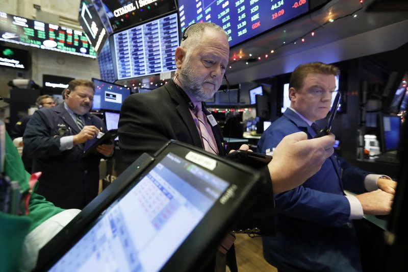 Trader Robert Moran, center, works on the floor of the New York Stock Exchange, Monday, Dec. 3, 2018. Stocks are opening sharply higher on Wall Street, following gains in overseas markets after the U.S. and China struck a 90-day truce in their trade dispute. (AP Photo/Richard Drew)