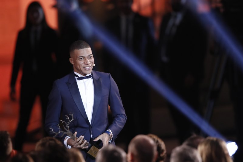 Paris St Germain's Kylian Mbappe celebrates with the Kopa Trophy during the Golden Ball,