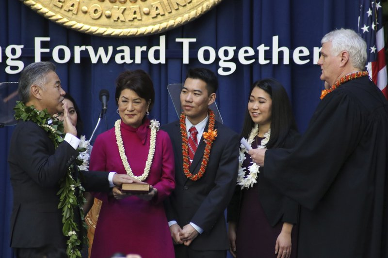 Hawaii Supreme Court Chief Justice Mark Recktenwald, right, swears in Gov. David Ige, left, as Amy Ige, Dawn Amano Ige, Matthew Ige and Lauren Ige, center left to right, look on at the Hawaii State Capitol in Honolulu on Monday, Dec. 3, 2018. Gov. Ige took the oath of office for a second term as Hawaii's governor. (AP Photo/Audrey McAvoy)