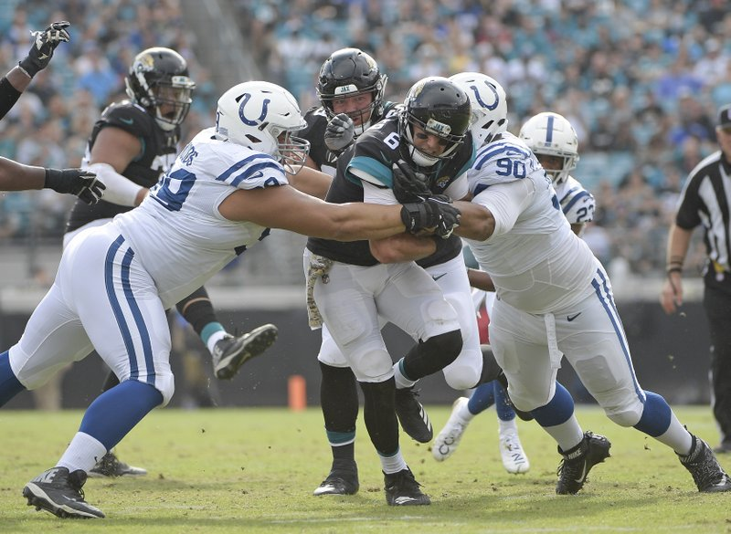 Jacksonville Jaguars quarterback Cody Kessler (6) gains yardage before he is stopped by Indianapolis Colts defensive tackle Al Woods, left, and defensive tackle Grover Stewart (90) during the first half of an NFL football game, Sunday, Dec. 2, 2018, in Jacksonville, Fla. (AP Photo/Phelan M. Ebenhack)