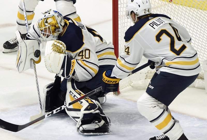 Buffalo Sabres goaltender Carter Hutton (40) stops a shot against the Nashville Predators as defenseman Lawrence Pilut (24), of Sweden, watches during the first period of an NHL hockey game Monday, Dec. 3, 2018, in Nashville, Tenn. (AP Photo/Mark Zaleski)