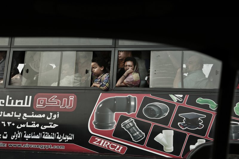 FILE - In this Tuesday, Oct. 18, 2016, file, photo, commuters ride a public bus as they wait in traffic, in Cairo, Egypt. Uber is launching a new minibus service on Tuesday, Dec. 4, 2018, in traffic-mad Cairo, Egypt's capital and the ride-sharing U.S. giant's fastest-growing market. (AP Photo/Nariman El-Mofty, File)