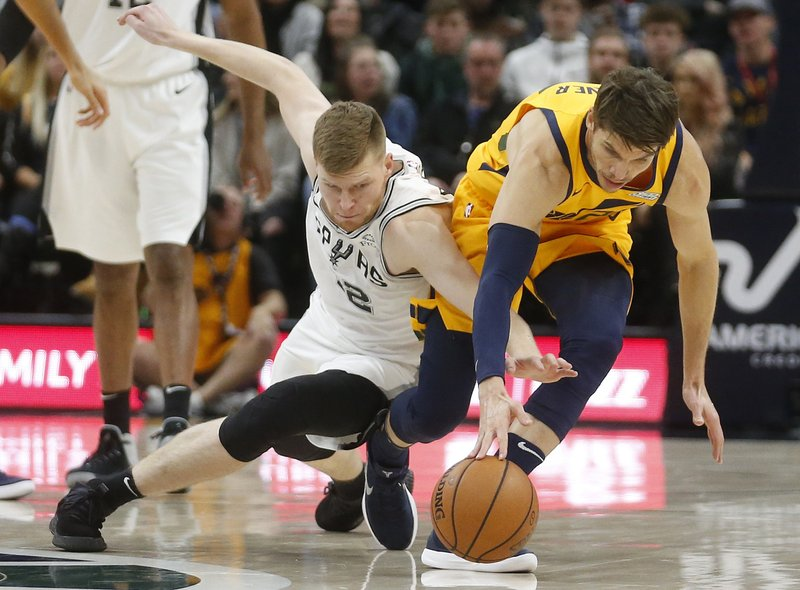 San Antonio Spurs forward Davis Bertans, left, and Utah Jazz guard Kyle Korver battle for a loose ball in the first half of an NBA basketball game, Tuesday, Dec. 4, 2018, in Salt Lake City. (AP Photo/Rick Bowmer)