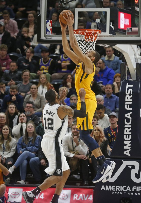 Utah Jazz center Rudy Gobert, right, dunks on San Antonio Spurs forward LaMarcus Aldridge (12) in the first half of an NBA basketball game, Tuesday, Dec. 4, 2018, in Salt Lake City. (AP Photo/Rick Bowmer)