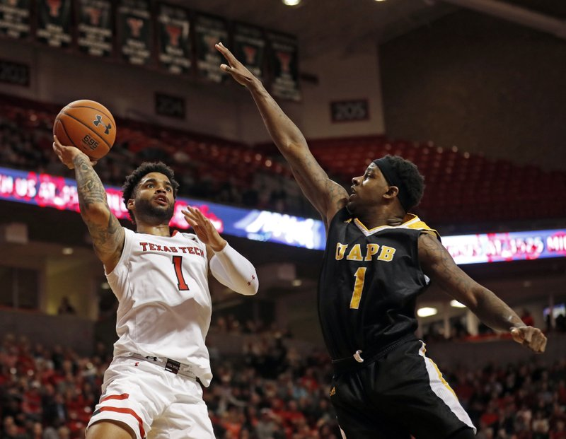 Texas Tech's Brandone Francis, left, shoots the ball around Arkansas-Pine Bluff's Charles Jackson during first half of an NCAA college basketball game, Wednesday, Dec. 5, 2018, in Lubbock, Texas. (AP Photo/Brad Tollefson)
