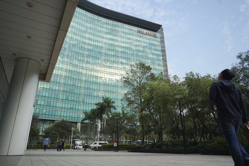FILE - In this March 13, 2018, file photo, a Huawei employee looks up as he walks toward the company's headquarters in Shenzhen in southern China's Guangdong Province. Canadian authorities said Wednesday, Dec. 5, 2018, that they have arrested the chief financial officer of China's Huawei Technologies for possible extradition to the United States. (AP Photo/Dake Kang, File)