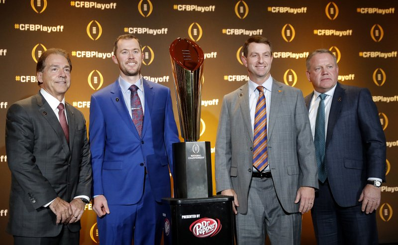Football coaches Nick Saban, of Alabama; Lincoln Riley, of Oklahoma; Dabo Swinney, of Clemson; and Brian Kelly, of Notre Dame, from left, pose with the college football championship trophy after a news conference Thursday, Dec. 6, 2018, in Atlanta. The four teams are in the College Football Playoff. (AP Photo/John Bazemore)