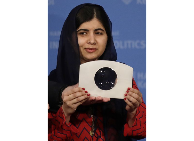 2014 Nobel Laureate Malala Yousafzai holds up the 2018 Gleitsman Activist Award while being honored prior to an address at the Kennedy School's Institute of Politics at Harvard University in Cambridge, Mass., Thursday, Dec. 6, 2018. (AP Photo/Charles Krupa)