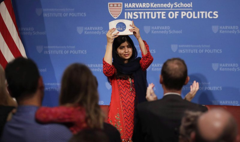 2014 Nobel Laureate Malala Yousafzai holds up the 2018 Gleitsman Activist Award as the audience applauds at the Kennedy School's Institute of Politics at Harvard University in Cambridge, Mass., Thursday, Dec. 6, 2018. (AP Photo/Charles Krupa)