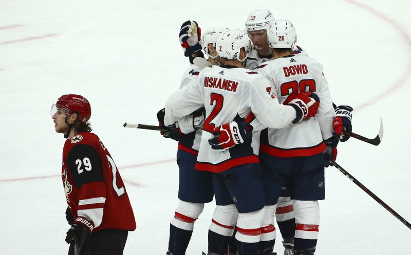 Washington Capitals defenseman Matt Niskanen (2) celebrates his goal against the Arizona Coyotes with Nic Dowd (26), Dmitrij Jaskin (23) and Dmitry Orlov as Coyotes right wing Mario Kempe (29) skates away during the second period of an NHL hockey game Thursday, Dec. 6, 2018, in Glendale, Ariz. (AP Photo/Ross D. Franklin)