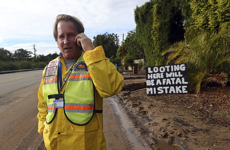 Kirby Kotler, who has lived in his home on Pacific Coast Highway for all of his 57 years, talks about how he first saved his home in the Woolsey Fire, then kept flooding from taking it in recent rains in Malibu, Calif. (AP Photo/Reed Saxon)